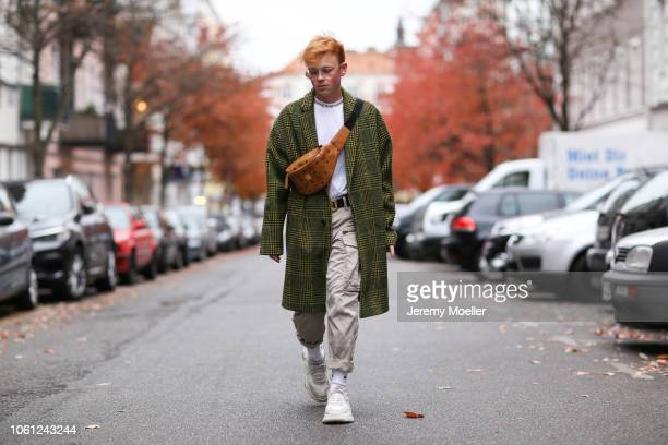 Erik Scholz wearing a MCM bag 032c belt Acne Studios shirt Balenciaga triple S and an Asos coat on October 28 2018 in Berlin Germany