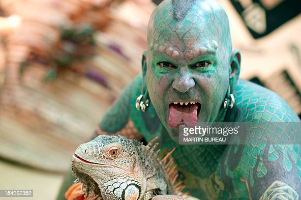 US Erik Sprague also known as The Lizardman poses with an iguana during the launching of the book Le Big Livre de l'Incroyable on October 17 2012 in...