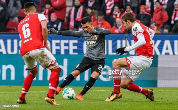 Erik Thommy of Augsburg in action against Danny Latza of Mainz and Stefan Bell of Mainz during the Bundesliga match between 1 FSV Mainz 05 and FC...