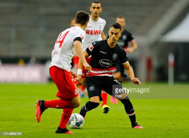 Erik Thommy of Fortuna Dusseldorf battles for possession with Noah Katterbach of FC Cologne during the Bundesliga match between 1. FC Koeln and...
