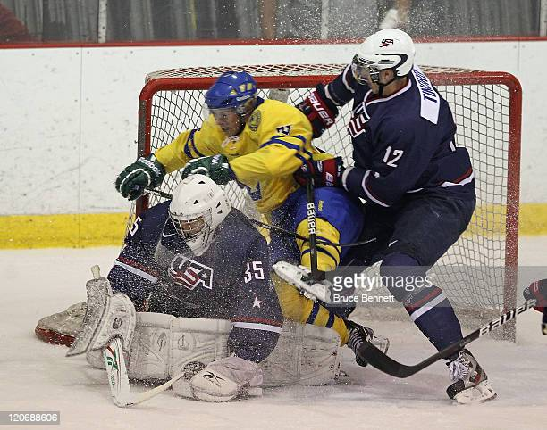 Erik Thorell of Team Sweden is checked into goaltender Stephan Michalek of Team USA by Jared Tinordi at the Lake Placid Olympic Center on August 8...