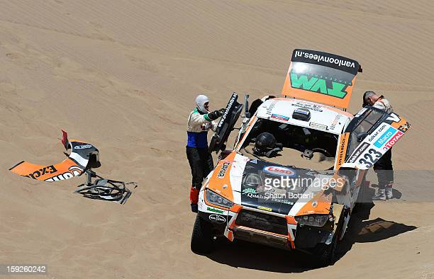Erik Van Loon and codriver Marc Wams of team HRX inspect their car after crashing during stage 6 from Arica to Calama during the 2013 Dakar Rally on...