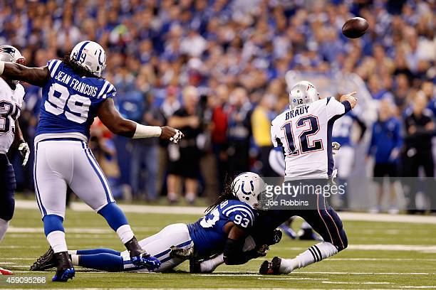 Erik Walden of the Indianapolis Colts tackles Tom Brady of the New England Patriots during the first half of the game at Lucas Oil Stadium on...