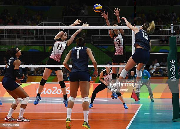 Erika Araki and Saori Kimura of Japan jump for a block while Kelly Murphy of the United States spikes the ball during the Women's Quarterfinal match...