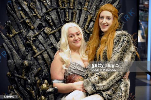 Erika Attaya and Rachel Howell sit together in the Iron Throne at a HBO Game of Thrones final season promotional event at Primark Boston where people...