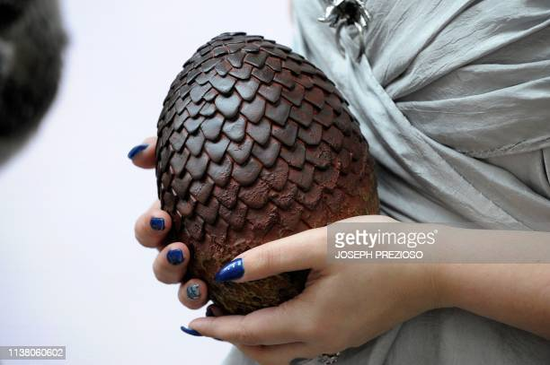 Erika Attaya dressed as the mother of dragons Daenerys Targaryen holds a dragon egg while waiting in line at a HBO Game of Thrones final season...