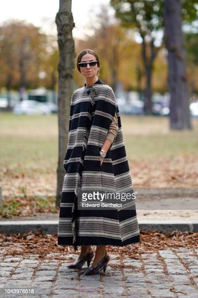 Erika Bodrin wears sunglasses a striped poncho dress outside Akris during Paris Fashion Week Womenswear Spring/Summer 2019 on September 30 2018 in...