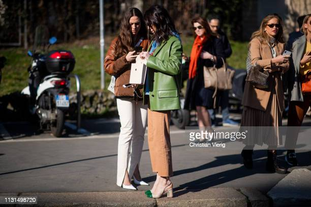 Erika Boldrin and Deborah Reyner Sebag wearing green jacket is seen wearing brown puffer jacket pants with slit white bag outside Tods on Day 3 Milan...