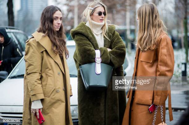 Erika Boldrin Camille Charriere and Monica Ainley talking and writing a text message on their pone wearing grenn teddy coat bag leather coat is seen...