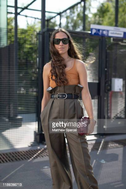 Erika Boldrin is seen on the street during Paris Haute Couture Fashion Week wearing Acne Studios orange top with highwaisted olive green pants and...