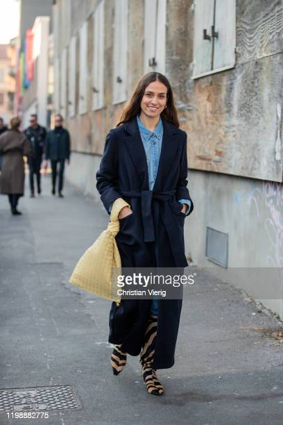 Erika Boldrin seen wearing navy belted coat, yellow bag, boots with animal print outside Marni during Milan Men Fashion Week Fall Winter 2020/2021 on...