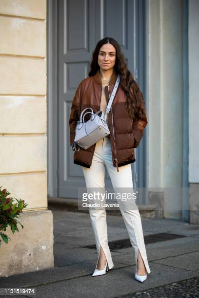 Erika Boldrin wearing brown puffer jacket pants with slit and white bag is seen outside Tod's on Day 3 Milan Fashion Week Autumn/Winter 2019/20 on...
