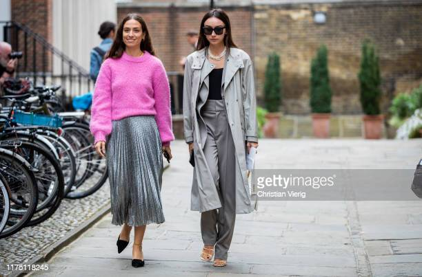 Erika Boldrin wearing pink knit silver pleated skirt and Beatrice Gutu wearing grey trench coat pants is seen outside Erdem during London Fashion...