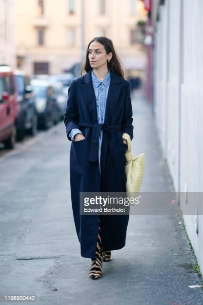 Erika Boldrin wears a blue denim shirt, a navy blue long coat, zebra print boots, a bag, earrings, outside Marni, during Milan Fashion Week...