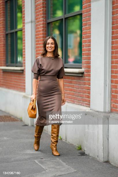 Erika Boldrin wears a gold large chain FF necklace from Fendi, a brown puffy short sleeves / belted / midi tube dress, a brown shiny leather Fendi...
