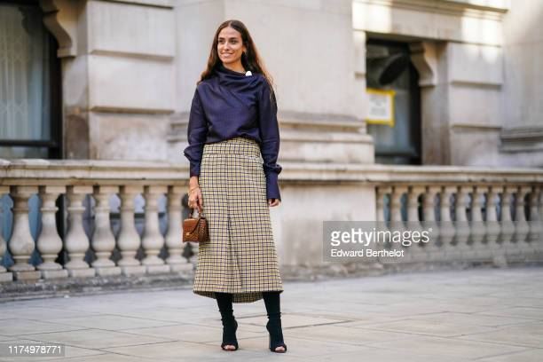 Erika Boldrin wears a navy blue top a brown checked skirt a brown leather bag boots during London Fashion Week September 2019 on September 15 2019 in...