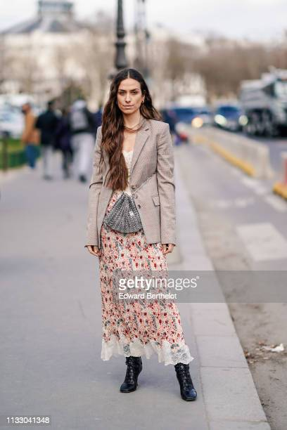 Erika Boldrin wears a necklace, a beige Prince of Wales check jacket, a beige floral print lace hemmed pleated skirt, a shiny metal mesh purse, black...