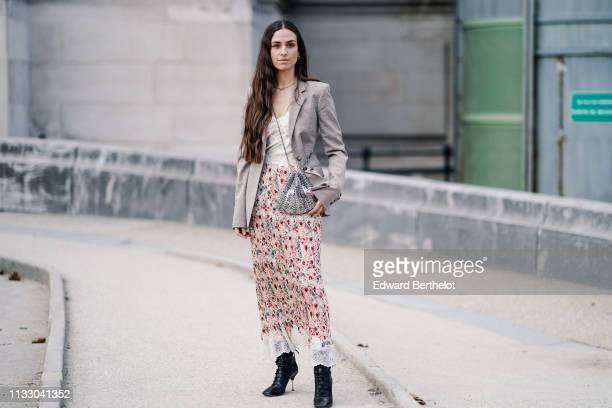 Erika Boldrin wears a necklace a beige Prince of Wales check jacket a beige floral print lace hemmed pleated skirt a shiny metal mesh purse black...