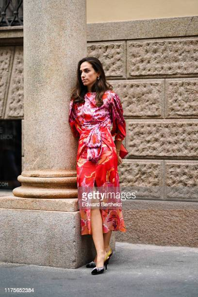 Erika Boldrin wears a red and pink floral print dress a clutch shoes outside the Peter Pilotto show during Milan Fashion Week Spring/Summer 2020 on...