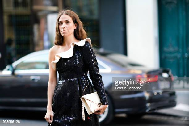 Erika Boldrin wears an offshoulder glitter black dress a white bag outside Valentino during Paris Fashion Week Haute Couture Fall Winter 2018/2019 on...