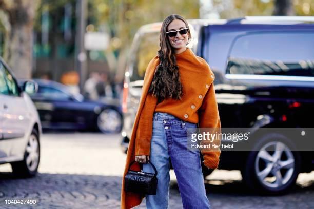 Erika Boldrin wears an orange oversized pullover blue flare jeans a black bag outside Koche during Paris Fashion Week Womenswear Spring/Summer 2019...