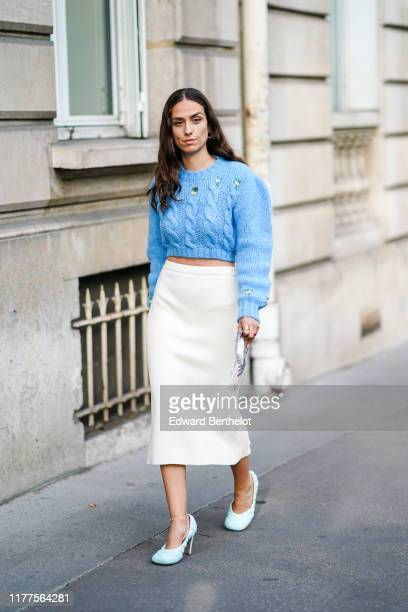 Erika Boldrin wears earrings, a blue knit long sleeves crop sweater, a cream-color skirt, a glittering metal mesh bag, white quilted heels, outside...