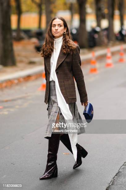 Erika Boldrin wears earrings, a checked brown blazer jacket, a white top with a long scarf, a gray skirt, leather boots, a blue bag, outside Chloe,...