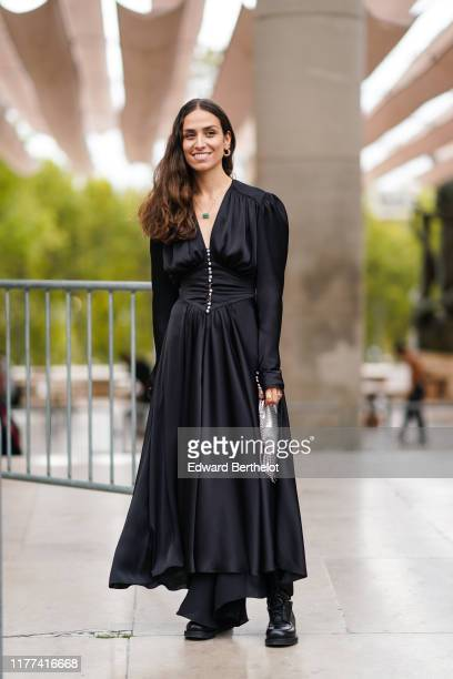 Erika Boldrin wears earrings a necklace a black princess waist long dress with bejeweled buttons black laceup shoes a shiny metal mesh bag outside...
