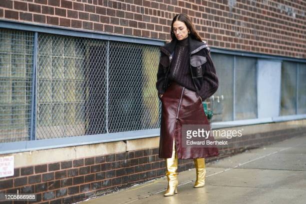Erika Boldrin wears glasses, a brown jacket, an oversized wool pullover, a brown leather skirt, golden shiny boots, outside Coach, during New York...