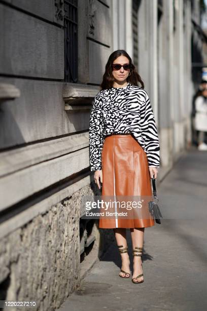 Erika Boldrin wears sunglasses, a black and white zebra print top, a brown leather skirt, shoes, a bag, outside Tod's, during Milan Fashion Week...