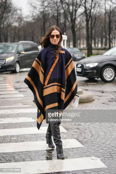 Erika Boldrin wears sunglasses, a blue and orange plaid wool poncho from Chloe, black leather boots, outside Chloe, during Paris Fashion Week -...