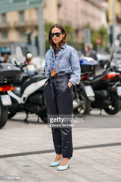 Erika Boldrin wears sunglasses a blue denim shirt black leather pants shoes a brown mini bag outside the Sportmax show during Milan Fashion Week...