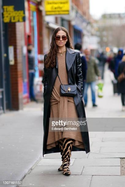 Erika Boldrin wears sunglasses, a brown wool long dress, a black leather long coat, a bag, zebra print brown and black striped boots, during London...
