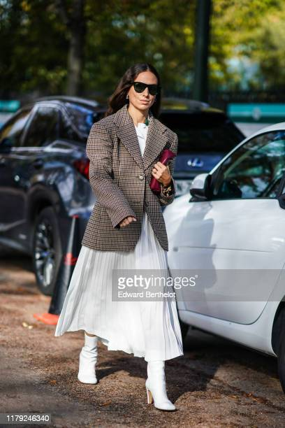 Erika Boldrin wears sunglasses, a checked oversized blazer jacket, a white pleated skirt, a burgundy clutch, white boots, outside Lacoste, during...