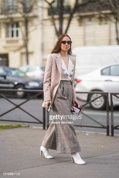 Erika Boldrin wears sunglasses, a pale pink blazer jacket, a white low neck shirt, checked large flared pants, white boots, outside Miu Miu, during...
