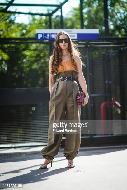 Erika Boldrin wears sunglasses an orange top khaki Acne Studios baggy pants a purple clutch black gladiator sandals outside Acne during Paris Fashion...