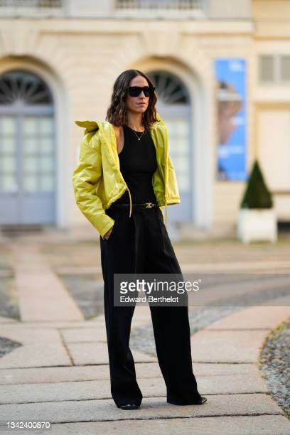 Erika Boldrin wears sunglasses, silver large pendant earrings, a gold chain necklace, a black high-neck tank-top, a black shiny leather Celine belt,...