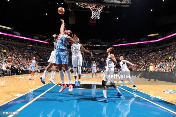 Erika de Souza of the Atlanta Dream grabs for the rebound against Monica Wright and Rebekkah Brunson of the Minnesota Lynx in Game Two of the 2011...