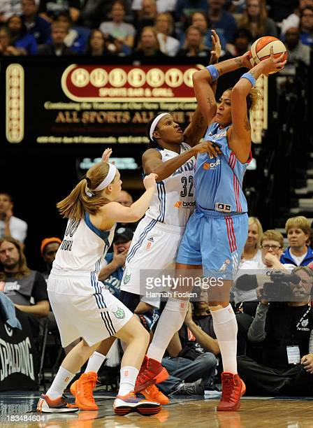 Erika de Souza of the Atlanta Dream passes the ball over Lindsey Moore and Rebekkah Brunson of the Minnesota Lynx during the third quarter of Game...