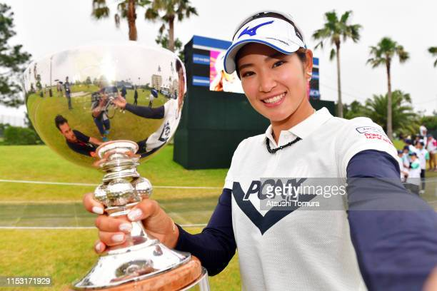 Erika Hara of Japan imitates a selfie with the tophy after the award ceremony following the final round of the Resorttrust Ladies at Grandi Hamanako...