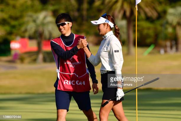 Erika Hara of Japan shakes hands with her caddie after winning the tournament on the 18th green during the final round of the JLPGA Tour Championship...