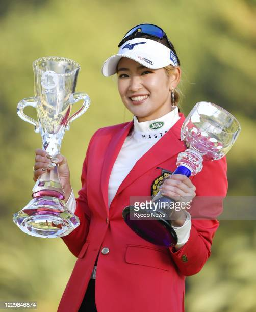 Erika Hara smiles with her trophies after winning the JLPGA Tour's Ricoh Cup on Nov. 29 at Miyazaki Country Club in Miyazaki, southwestern Japan.