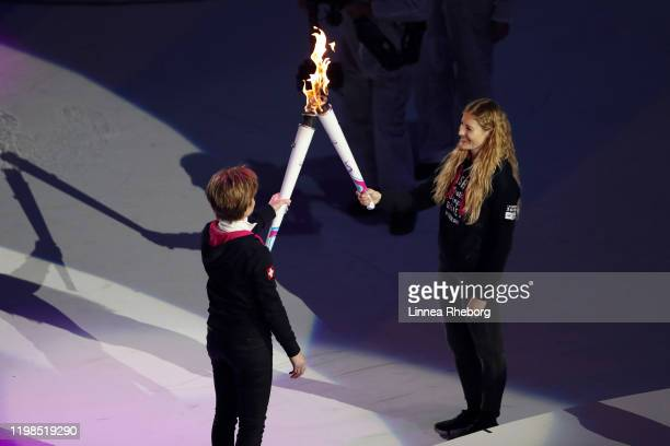 Erika Hess hands over the torch to Fanny Smith during the Opening Ceremony of the Lausanne 2020 Winter Youth Olympics on January 09, 2020 in...