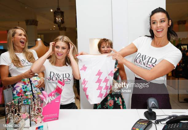Erika Heynatz and Natalie Bassingthwaighte look on as Megan Gale serves customers at David Jones Shop Pink Donation Day 2013 for Breast Cancer...