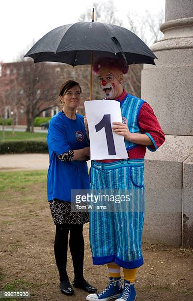 Erika Masonhall from the office of Sen Joe Lieberman IConn and a clown take shelter from the rain before democratic staffers battled republican...