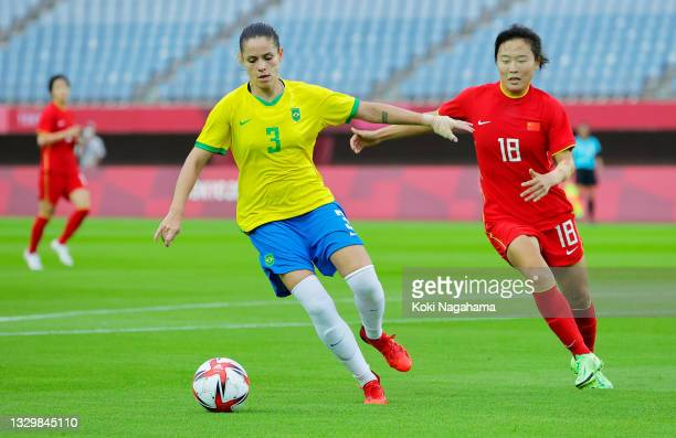 Erika of Team Brazil battles for possession with Wurigumula of Team China during the Women's First Round Group F match between China and Brazil...