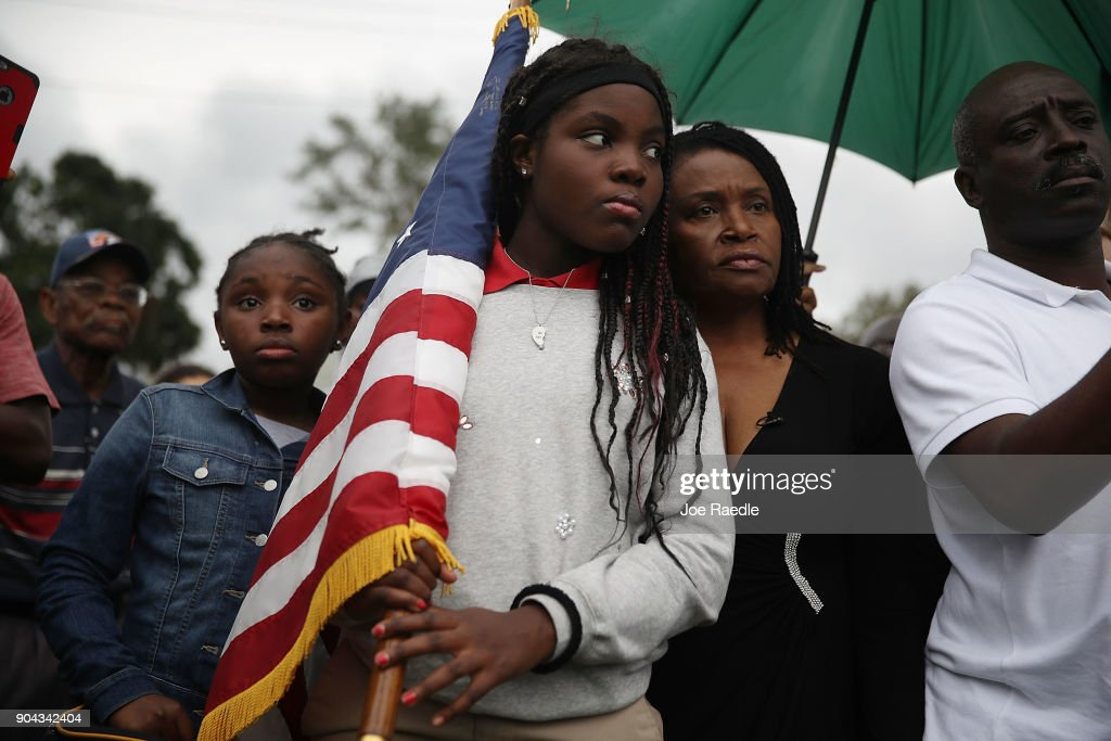 Erika Rigaud,15, holds an American flag as she joins with others to mark the 8th anniversary of the massive earthquake in Haiti and to condemn President Donald Trump's reported statement about immigrants from Haiti, Africa and El Salvador on January 12, 2018 in Miami, Florida. President Trump is reported to have called those places 'shithole countries' whose inhabitants are not desirable for U.S. immigration.