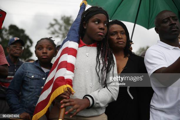 Erika Rigaud holds an American flag as she joins with others to mark the 8th anniversary of the massive earthquake in Haiti and to condemn President...