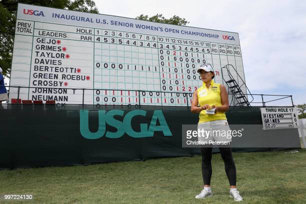 Eriko Gejo of Japan stands in front of the leader board during the first round of the US Senior Women's Open at Chicago Golf Club on July 12 2018 in...