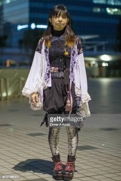 Eriko Nemoto wearing a white capelet a mesh black shirt pinstripe black nickers with lace trim by Cutie Flash black and white leggings a apple...